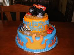 "Monster Truck cake - This is a 10"" cake and 6"" iced in buttercream.  Flames, flags, and rocks are fondant.  Truck and cars are toys."
