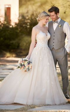 This ball gown from Essense of Australia is a bold twist on a timeless look, featuring a beaded lace bodice secured with illusion straps. The full tulle skirt swings gracefully into a beautiful court train. The back zips up with ease under sparkling crystal buttons.