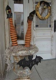 Halloween porch decoration - Upside down witch in garden urn with a hanging bat