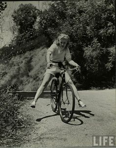 Girl bicycling circa the 1940s or 1950s