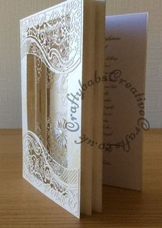 Full tutorial on web site for 3D Frame Wedding Card made using a variety of dies including; Tattered Lace large Panorama dies and nesting rectangles, Tattered Lace double delight adore, Sparkle corner die, Spellbinders Blooms 1, and Flourish from Spellbinder flower bundle set. Britannia Sentiment dies.