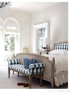 Gorgeous white bedroom with blue and white buffalo check headboard and bench - French farmhouse charm