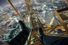 Long way down: The craze involves thrill seekers climbing to the top of city skyscrapers and taking pictures of the spectacular view beneath...