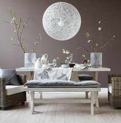 The wall's rich tone gives the space warmth without dampening it's light, airy feel. A picnic-style table paired with boxy wicker chairs evokes the pleasure of dining al fresco, while luxe accents, such as metallic and grey-velvet pillows, keep the look elegant.