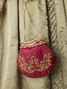 A reticule bag of crimson silk decorated with cream silk ribbon, and an embroidered motif. The bag closes with a cord drawstring.  Small bags such as reticules, miser's purses and other types, grew in popularity from the early nineteenth century. Previously, detachable pockets fitted easily under large skirts. When fashion slimmed, women began to carry their everyday articles in external purses. After wide skirts returned purses became mainly for decoration, perhaps to match a bonnet or…