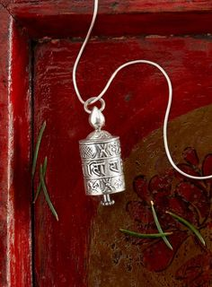 Tibetan Prayer Wheel Necklace - Send healing thoughts into the world with each turn of this sterling silver prayer wheel necklace. The drum is decorated with the sacred mantra Om Mani Padme Hum, the traditional Tibetan Buddhist chant for healing and compassion. Inside, a paper scroll printed with hundreds of the same mantra multiplies the effect of sending your prayers.