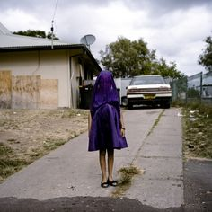 """Photographer Raphaela Rosella created a portrait of a """"socially isolated"""" girl named Laurinda in a disadvantaged community in Moree, New South Wales, Australia. She was wearing a purple dress and waiting for a bus to go to Sunday School. World Press Photo of the Year 2014 #Petapixel  #photojournalism #bullying #outcast"""