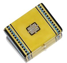 ART DECO ENAMEL AND DIAMOND VANITY CASE, CHARLTON & CO., CIRCA 1925.  The hinged rectangular case applied with yellow enamel, the sides decorated in blue and black enamel bands and zig-zag motifs, the lid surmounted by a rose-cut diamond monogram, the thumbpiece set with a pearl, opening to reveal a cigarette compartment with clip and two covered compartments for a lipstick case and powder, the latter with mirror on inside lid, 3 1/8 by 2 3/8 inches, signed Charlton & Co.