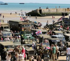 Public: Crowds, surrounded by Second World War vehicles, gather on Gold Beach in Arrommanche. They are stood on the same spot thousands of s...