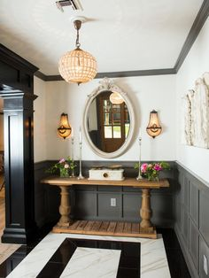 Sara's tastes run toward a nouveau classical look with an affinity for ornate furnishings and French antiques. The combination presented a decorating challenge for Joanna who frequently leans more in the direction of farmhouse country and rustic themes. This new foyer – highlighted by black and white marble floors, rich textures and dark gray paneling – offers a mix of contemporary elements and old world touches making for a carefully integrated look that marries comfort and style.