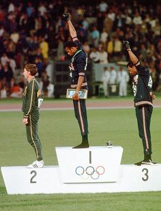 American sprinters Tommie Smith (center) and John Carlos (right) raise their black-gloved fists on the Olympic medal podium in Mexico City to signify Black Power. Smith, the gold medalist in the 200-meter race, and Carlos, the bronze medalist, were kicked out of the Games for their overtly political statement.
