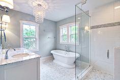Calming master bathroom with carrara marble floors, freestanding pedestal tub, large double sink white vanity, huge tiled shower, and glass links chandelier