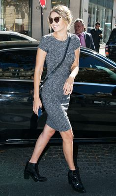Gigi Hadid wears a body-con sweaterdress with  mirrored sunglasses, a crossbody bag, and ankle boots