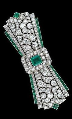 Fine French Art Deco Diamond and Emerald Bow Brooch This highly stylized bow knot pin incorporates modern geometrical flair contrasting with floral ornamentation a' la the great French jewelry masters circa 1925. The central Colombian emerald is enhanced with fine emerald calibre borders which accent the high quality melange of of sparkling white diamonds in the pierced center plaque. An original Deco delight; 2 1/2 inches in width.