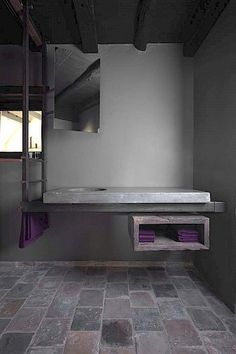 grey bathroom with purple accents - paired back with a raw edge