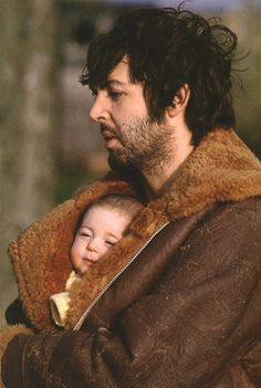 A sleep deprived daddy (Paul McCartney) with his wee baby peeking from his jacket. Love this pic.