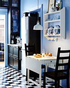 Malý stolík IKEA s vyklápacou časťou a dvoma stoličkami. Nad ním na stene polica na uloženie tanierov.