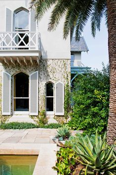The classic Gothic revival house is accented by the newly transplanted Canary Island date palm. The palm was just one super-advanced plants freighted down from Sydney to provide instant impact and maturity.