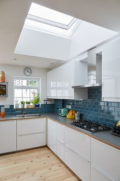 Bring daylight into your kitchen with a new VELUX roof window. This kitchen has been modernised using white cabits, blue tiles and an orange accent to the worktops. Open Plan Kitchen, New Kitchen, Kitchen Modern, Kitchen Living, Kitchen Tiles, Kitchen Design, Kitchen Windows, Modern Roofing, Roof Window