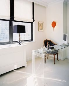 A black-and-white office space with a Lucite desk. Interior Design: Laura Garcia