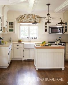 A beadboard backsplash, farmhouse-style sink, and a copper triple-pendant light fixture above the island contribute to the cottage feel.