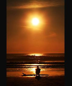 A surfer watches the sunset at Croyde Bay, North Devon