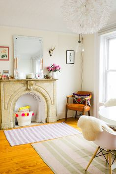 A fashionable and gorgeous feminine living room with marble fireplace and pops of bold color