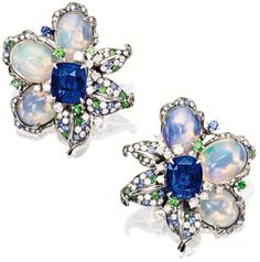 Sapphire, opal, and diamond earrings. Of floral design, each flower head centring on a cushion-shaped sapphire altogether weighing approximately 10.00 carats, highlighted by three jelly opal petals altogether weighing approximately 17.20 carats, embellished by leaves set with circular-cut diamonds, sapphires and tsavorite garnets, mounted in 18 karat blackened and white gold. Via Sotheby's.