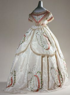 "Evening Dress, 1864. A dress in the crinoline style. The embroidery is arranged over the skirt. The bodice, the waist, and the panels on the back of the skirt are trimmed with delicate fringes. During the 19th century, men's fashion became functional and in-ornate, while women's wardrobes appeared more lavish than ever. Trimming like fringes, tassels and braids (""passementerie"") that required a lot of attention to detail appeared in numerous variations."