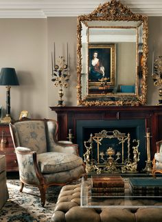 Love the gilt and brass accents - oversized mirror, fire screen, candlesticks, lamp combined with light brown walls, black and blue