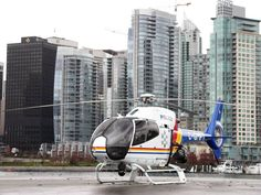 RCMP E-Division helicopter parked in Stanley Park showing downtown Vancouver in the background, photo by PoliceHotels.com