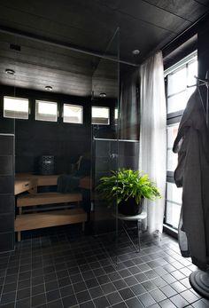 Saunan pesuhuoneen katto on Helo Decon mustaa Taika-koivupaneelia ja lattia Pukkilan Via Emilia Nero 440510 -laattaa. Kylpytakit ovat Lapuan Kankureilta.