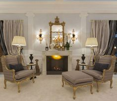 Luxurious interior with gorgeous hand-crafted Chippendale mirror, Louis XV armchairs, stately fireplace mantel and fluted pilasters; living room decoprating ideas; luxury interiors inspiration