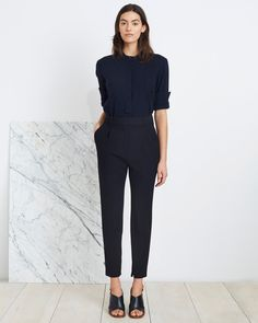 Maintain a sleek silhouette with Apiece Apart's Palace Tapered Trouser in Black. This high-waisted trouser with front pleats feature a narrow, tapered leg, with an invisible zipper at the inner ankle,
