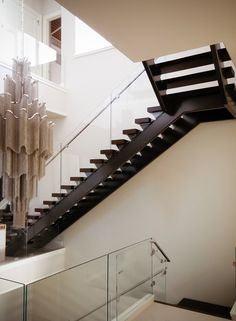 Luxury residential open rise, contemporary stair design featuring an elegant glass and stainless steel handrail system.