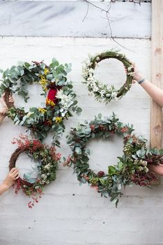Pretty holiday wreath making DIY with eucalyptus, berry branches and colorful flowers on pre-made wicker wreaths -- such a fun, customizable holiday DIY!