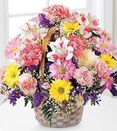 This cheery basket is a welcome sight! Bright and fluffy pink carnations, lavender and yellow daisy pompons, with white and purple accents are arranged in a handled basket.  It's the perfect gift for any occasion.
