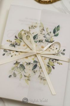 This vellum wedding invitation features a luxurious translucent vellum jacket with unique floral that will impress your guests, secured with a wax seal in gold. The invitation comes with the ribbon and wrap.