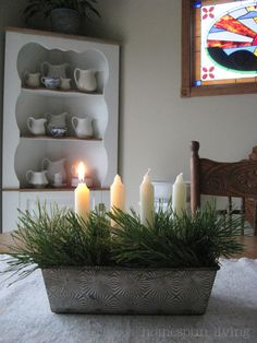 Pine needles and candles in a vintage bread pan.