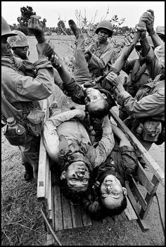 "Philip Jones Griffiths.  1973. Cambodia. Soldiers of the U.S.-supported Lon Nol government ""removing the bodies of their fallen comrades from the battlefield""."