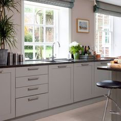 Kitchen with pale wood floor, soft grey units, black granite worktops and black bar stools Grey Kitchen Cupboards, Black Kitchen Countertops, Taupe Kitchen, Teal Kitchen Decor, Kitchen Worktop, Kitchen Units, Granite Worktops, Grey Cabinets, Black And Grey Kitchen