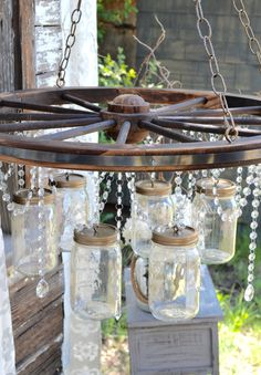 Rock me, mama, like one of these gorgeous wagon wheel decor ideas. Rock me, mama, like one of these gorgeous wagon wheel decor ideas. Mason Jar Light Fixture, Mason Jar Chandelier, Diy Chandelier, Mason Jar Lighting, Wagon Wheel Chandelier Diy, Rustic Light Fixtures, Outdoor Chandelier, Iron Chandeliers, Pendant Lamps