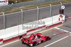 raceauto staat te wachten voor het rode stoplicht in de pitsstraat