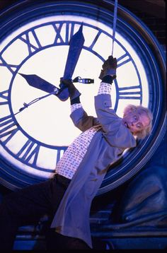 In Back to the Future Roy Doc Brown is seen hanging from a clock whose hands were pointing at a few minutes past ten. Back To The Future Party, The Future Movie, Marty Mcfly, Great Films, Good Movies, 80s Movies, Michael J. Fox, Science Fiction, April Fools Pranks