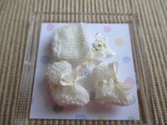 unknown artist - crocheted baby's white bonnet, and booties plus a rattle; sold for $14.95 on ebay
