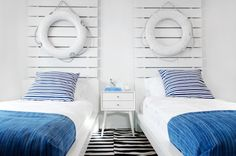 Nautical themed boys' room boasts tall white plank headboards adorned with white lifesavers on twin beds dressed in white and sea blue bedding flanking shared nightstand, West Elm Mid-century Nightstand, atop black and white striped rug.