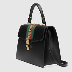 Shop the Sylvie medium top handle bag by Gucci. Our Sylvie bag in a beautiful top handle shape with our nylon Web embedded under the leather and decorated with a gold chain and buckle. Made in our smooth, classic leather. Black Handbags, Tote Handbags, Leather Handbags, Big Tote Bags, Backpack Bags, Mini Bags, Women's Bags, Gucci Sylvie Bag, Nylons
