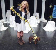 Maggie, was the ring bearer in the FFA-themed wedding. To showcase the FFA colors of blue and yellow, the dog's blue leash was adorned with yellow mums and ribbon.