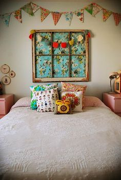 An old window frame with fabric but can easily put in other things. An old map, a piece of tapa cloth, a montage of family photos just tacked into the gaps as well as little objects. Love the patchwork of various cushions and the bunting above the bed.
