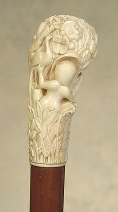 "A fantastic ivory cane of a nude in an elaborate marsh and garden scene. The ivory handle, fashioned in bec de corbin configuration, is carved with owner initials: ""G.L."". It is 4 1/2"" high and 2"" at its widest and it features a nude maiden who seems to be peering into a window. It is fraught with symbolism. There are standing cranes, a monkey's face, a standing elephant, and of course, a slithering snake.  (Is it Eve in the exotic Garden of Eden?  It is perhaps Continental, ca 1890"